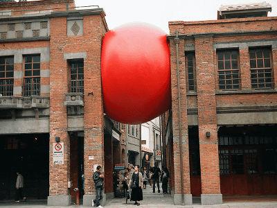 世界を旅する巨大な赤玉、日常に...